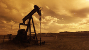 Oil well in front of a yellow backdrop.